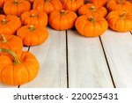 Autumn pumpkins forming a corner border against white wood - stock photo