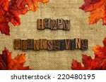 Happy Thanksgiving written with wooden letters on burlap with autumn leaves - stock photo