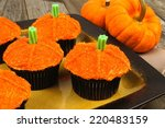 Pumpkin cupcakes on a plate on a wooden table - stock photo