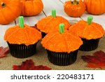 Pumpkin cupcakes with burlap on a wooden table - stock photo