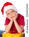 Sad boy with gift box in christmas hat, isolated on white - stock photo