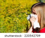 Young Woman Blowing Nose In...