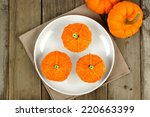 Above view of three pumpkin cupcakes on a plate with wood background - stock photo