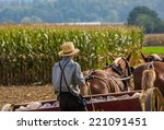 Small photo of Young amish farmer behind horses sowing a field during the fall season.