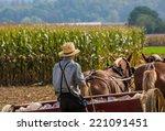 Young Amish Farmer Behind...