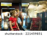 Small photo of mother and child looking ancient amphores in museum