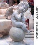 Stone statue of melancholic angel sitting on sphere - stock photo