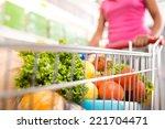woman at supermarket pushing a...