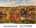 Stock photo beautiful fall reflections in a lake with a fishing boat during sunset 221795989