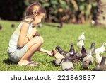 Little Girl Feeding Pigeons In...