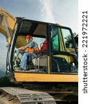 male worker operating excavator on construction site - stock photo