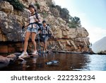 Small photo of An attractive hiking couple balancing on rocks to get across the water with copyspace