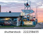 Small photo of TUCUMCARI, NEW MEXICO - SEPT 6, 2014: Motel Safari, a Route 66 icon, at sunset with neon signs and mural of Trailways tour bus with Tucumcari Tonite as its destination.