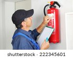Small photo of A Professional checking aFire extinguisher