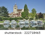 Collegiale de Notre-Dame at Dole (Jura, Franche-Comte, France) with at foreground the Doubs River and pleasure boats - stock photo