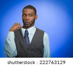 Small photo of Deceiver. Portrait young business man opening shirt to vent it's hot, unpleasant, awkward situation embarrassment isolated blue background. Negative emotion face expression feeling body language sign