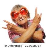 Stock photo senior woman wearing big sunglasses doing funky action isolated on white background 223018714