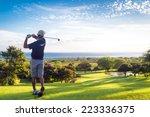 Man Hitting Golf Ball Down Hil...