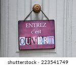 """sign at a shop with the french text: """"entrez c'est ouvert"""" that means """"come in we're open"""" - stock photo"""