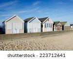 a row of wooden beach huts at...