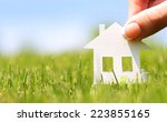 paper house in green grass over ... | Shutterstock . vector #223855165