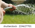 A Asian Man Watering The Garde...