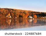 Rural scene during Fall or Autumn along the Saint John River in New Brunswick, with reflection of colorful trees along the water