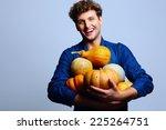 Smiling Man Holding Pumpkins...