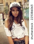 Small photo of Stylish pretty hipster swagger girl portrat. Outdoor fashion style portrait of young beautiful woman