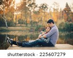 Small photo of Romantic couple relaxing on the river dock in autumn park