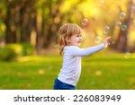 happy kids blow bubbles outdoors | Shutterstock . vector #226083949