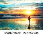 surfer walking on the beach in...   Shutterstock . vector #226259935