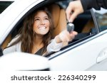Small photo of Young woman receiving the keys of her new car