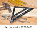 Carpenters tools and board on workbench surface - stock photo