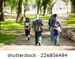 Stock photo rear view of university students with backpacks walking on campus road 226806484