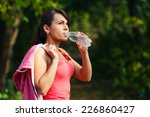 a girl drinks water after sport | Shutterstock . vector #226860427
