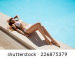Young Woman Sunbathing Near...