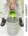 painter pouring green paint into a large bucket - stock photo