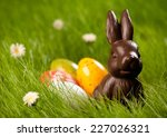 Small photo of Close up of colorful Easter eggs and chocolate bunny in fresh spring grass.