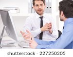 Small photo of two businessmen having discussion in office. over shoulder view of businessmen looking at each other and using laptop