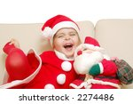 Little cute smiling girl dressed in santa clause costume playing with santa doll on sofa - stock photo