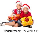 Two happy kids in Santa hats with Christmas gift box, isolated on white - stock photo