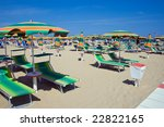 chaise longue and umbrellas on a sandy beach in Rimini, Italy - stock photo