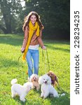 Stock photo beautiful young woman with four poodles in the park 228234235