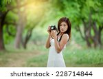 young lady with camera outside | Shutterstock . vector #228714844