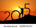 Silhouette person jumping over 2015 on the hill at sunset