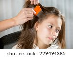 mother treating daughter's hair ... | Shutterstock . vector #229494385