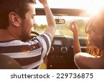Small photo of Young Couple Driving Along Country Road In Open Top Car