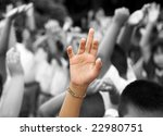 hand in color raised among others hands in black and white background