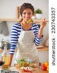 smiling woman preparing salad... | Shutterstock . vector #230743357